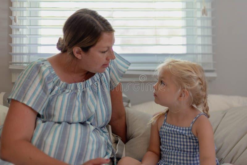 Giovane donna incinta che si siede sul letto che parla con la sua scuola materna a fotografia stock