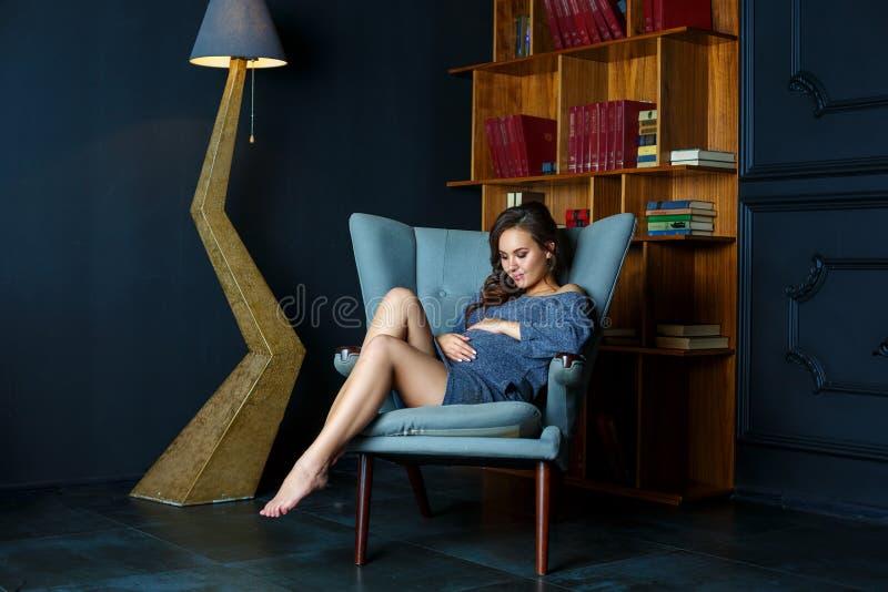 Giovane donna incinta che si siede in una sedia fotografia stock libera da diritti