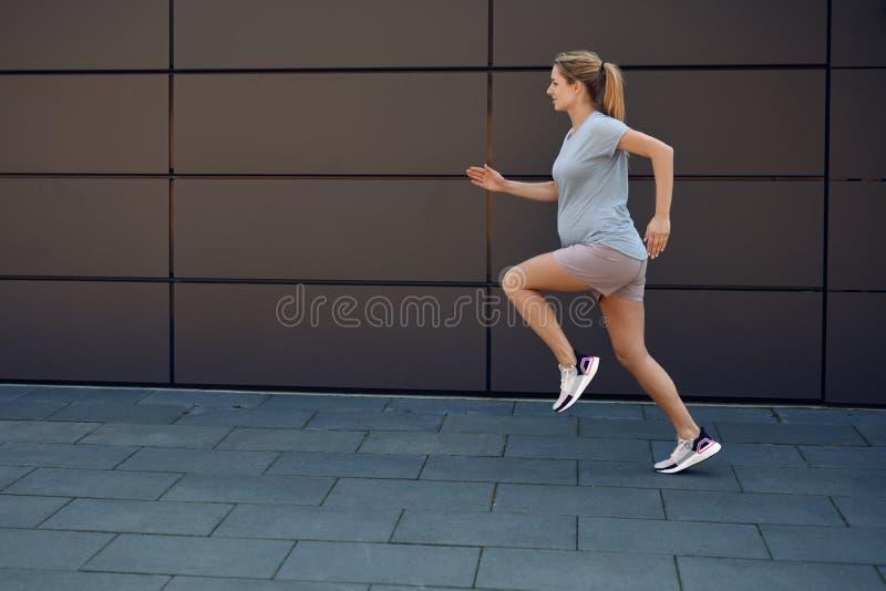 Giovane donna incinta che tiene sprintare adatto fotografie stock libere da diritti