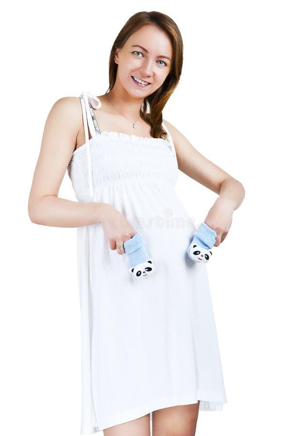 Giovane donna incinta con i calzini dei bambini sopra la sua pancia fotografia stock libera da diritti