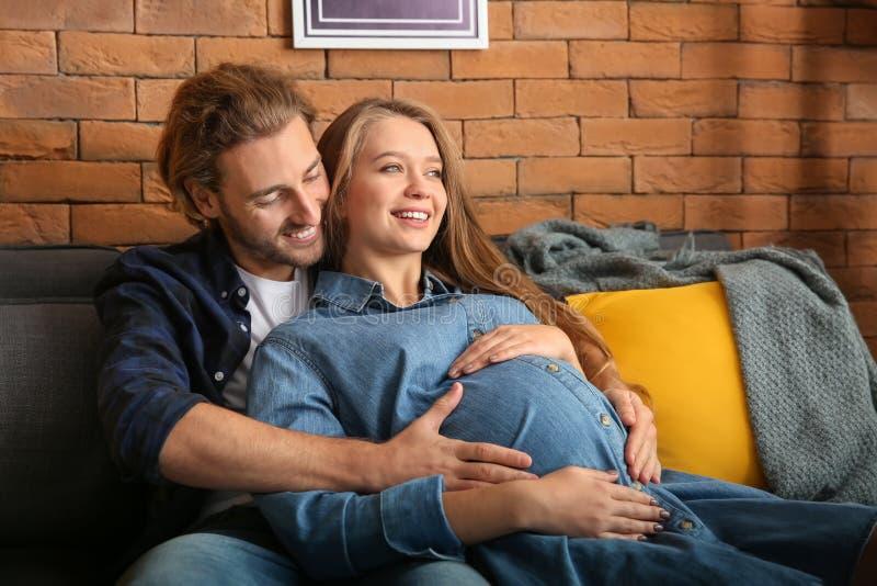 Giovane donna incinta con il suo marito a casa immagini stock