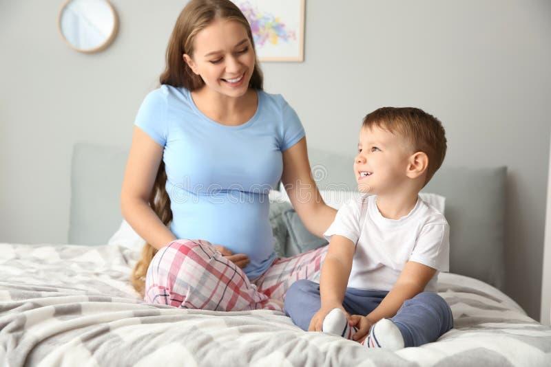 Giovane donna incinta con il suo piccolo figlio sveglio a casa immagini stock