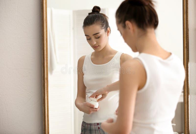 Giovane donna incinta con la crema di fronte nella mattina immagini stock