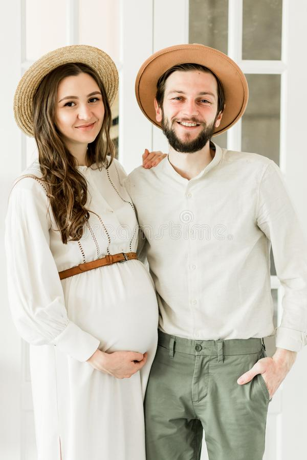 Giovane donna incinta graziosa ed il suo marito nella condizione del cappello vicino alla parete del cactus fotografie stock