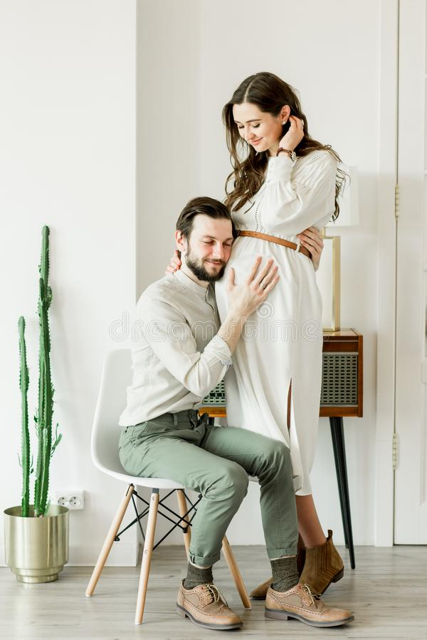 Giovane donna incinta graziosa ed il suo marito nella condizione del cappello vicino alla parete del cactus immagini stock