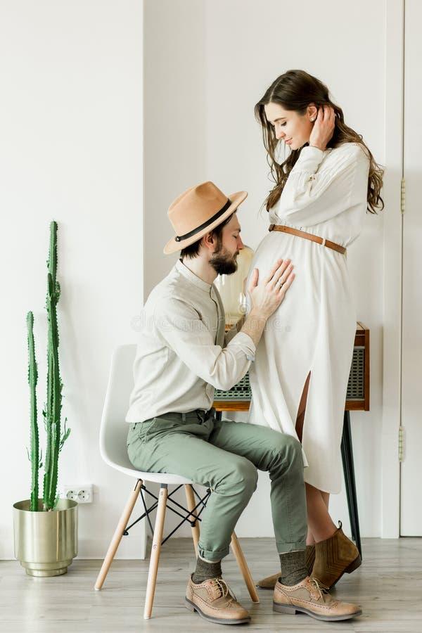 Giovane donna incinta graziosa ed il suo marito nella condizione del cappello vicino alla parete del cactus immagine stock