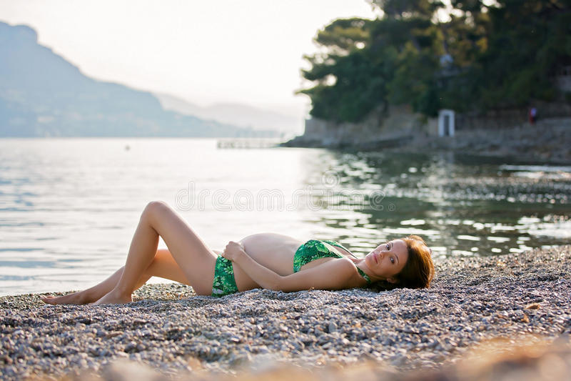 Giovane donna incinta sulla spiaggia su alba fotografie stock libere da diritti