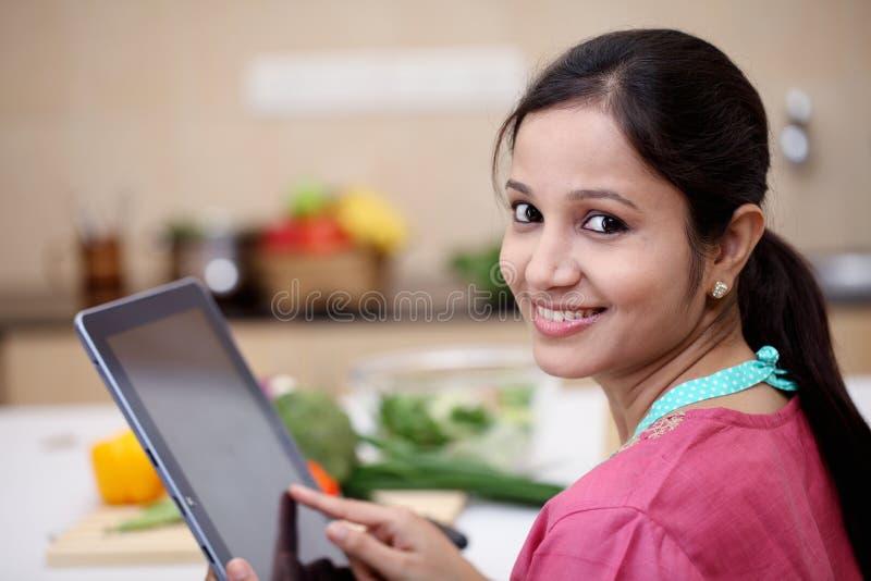 Giovane donna indiana che per mezzo di una compressa immagine stock