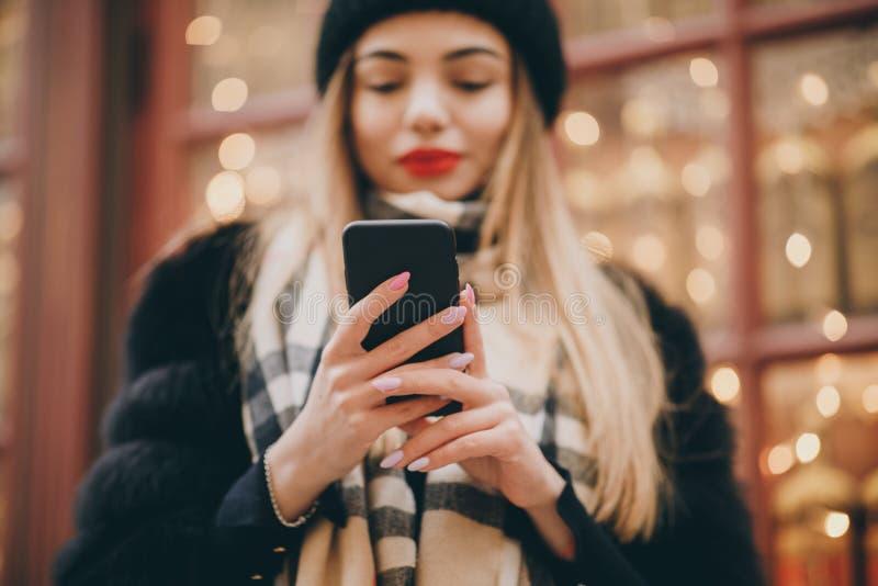 Giovane donna indossa il velo mentre cammina nel centro della città, usando smartphone Comunicazione, shopping online, sociale immagini stock libere da diritti