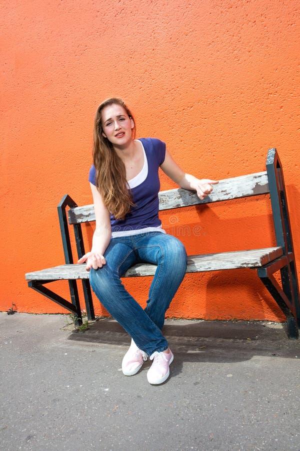Giovane donna infelice che si siede su un banco, protestare, esprimente preoccupazione immagine stock