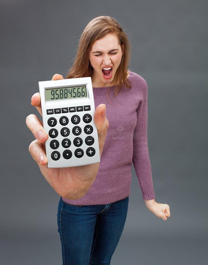Giovane donna infuriata che grida contro l'economia finanziaria sul calcolatore surdimensionato immagini stock