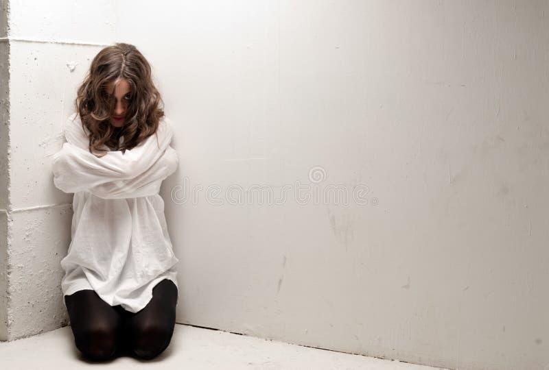Giovane donna insana con la camicia di forza sulle ginocchia immagini stock