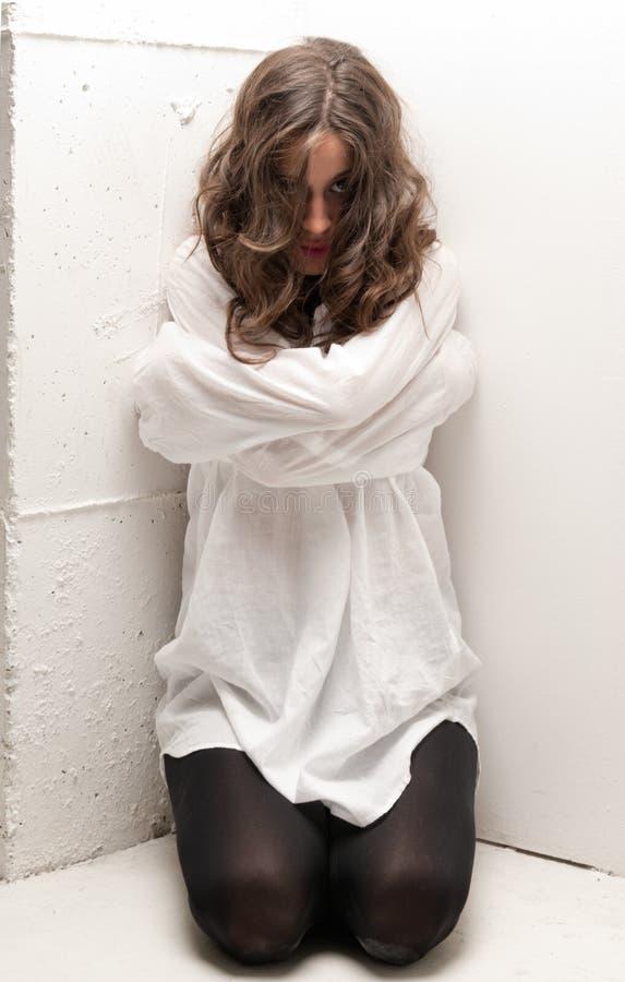 Giovane donna insana con la camicia di forza sulle ginocchia fotografia stock libera da diritti
