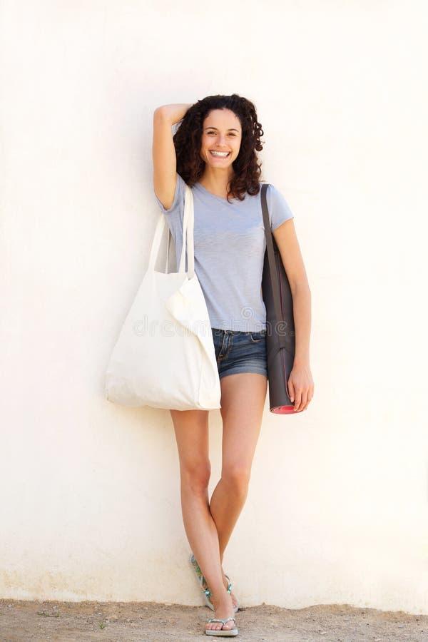 Giovane donna integrale che sorride con la stuoia e la borsa di yoga contro il fondo bianco fotografia stock libera da diritti