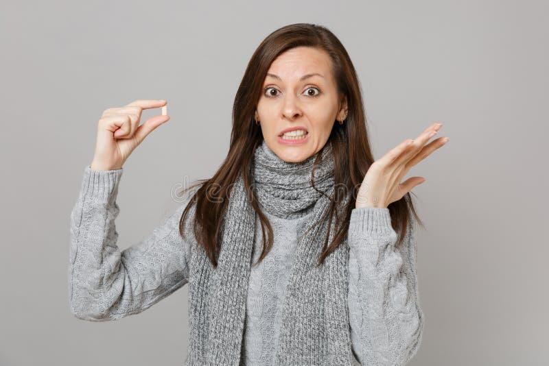 Giovane donna interessata in maglione grigio, mani di diffusione della sciarpa che tengono la compressa del farmaco, pillola di a immagine stock libera da diritti