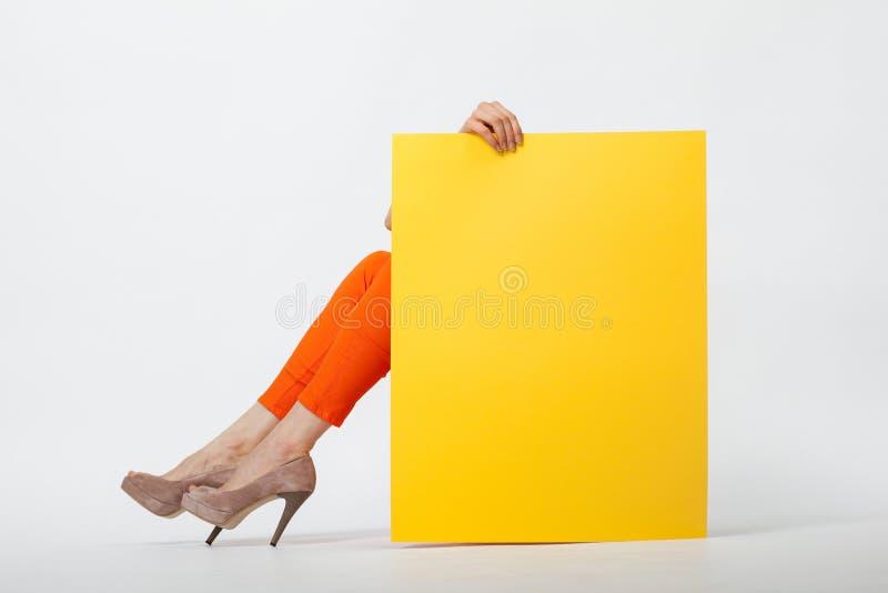 Giovane donna irriconoscibile in pantaloni arancio che tengono carta gialla immagine stock