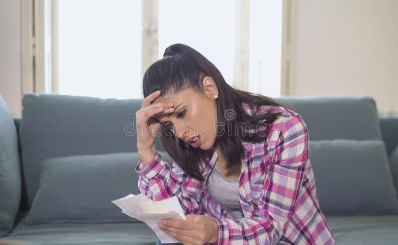 Giovane donna ispanica attraente e preoccupata che controlla le spese ed i pagamenti mensili delle carte di banca delle fatture n immagini stock