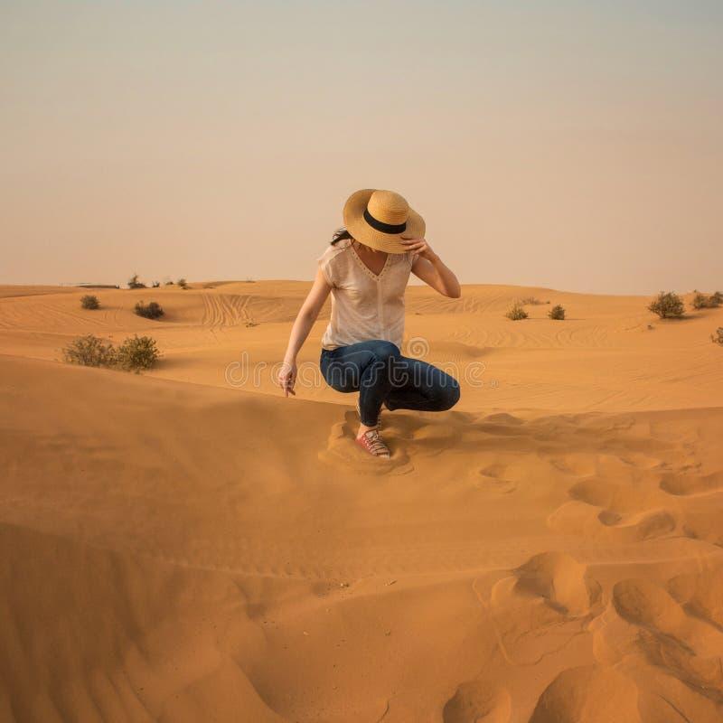 Giovane donna in jeans e cappello di paglia Ragazza nel deserto fotografie stock