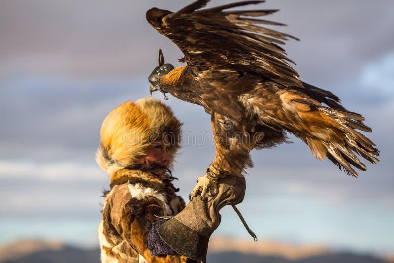 Giovane donna kazaka di Eagle Huntress Berkutchi con il cavallo mentre cercando alla lepre con le aquile reali sulle sue armi fotografia stock