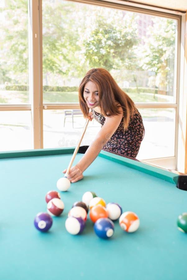Giovane donna latina attraente sorridente che gioca stagno fotografia stock