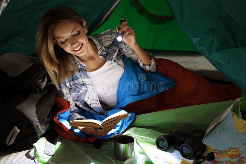 Giovane donna in libro di lettura del sacco a pelo immagine stock libera da diritti