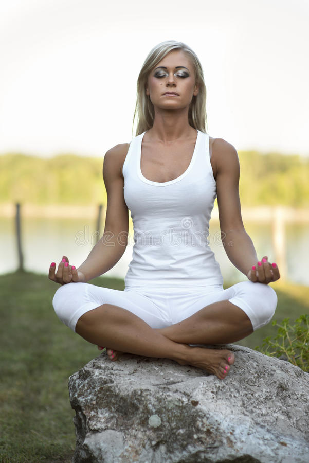 Giovane donna Lotus Yoga Position su roccia fotografia stock