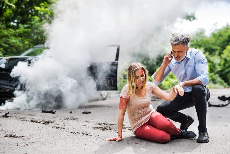 Giovane donna in macchina dopo un incidente e un uomo che fanno una telefonata immagine stock