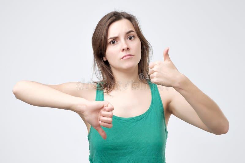 Giovane donna in maglietta verde che mostra i pollici su e giù il segno immagine stock