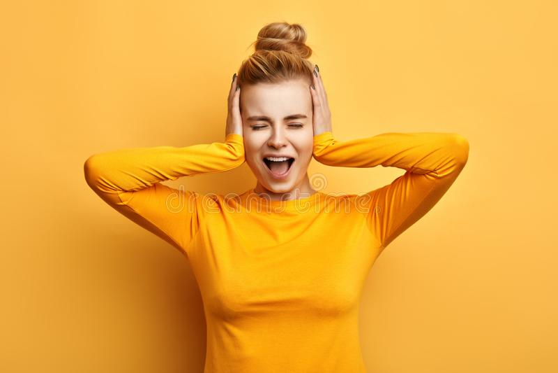 Giovane donna in maglione giallo alla moda che grida nel terrore con le mani sulle sue orecchie immagine stock libera da diritti
