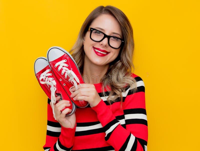 Giovane donna in maglione a strisce rosso con i gumshoes fotografia stock libera da diritti