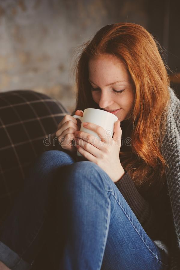 Giovane donna malata che guarisce con la bevanda calda a casa sullo strato accogliente fotografia stock libera da diritti