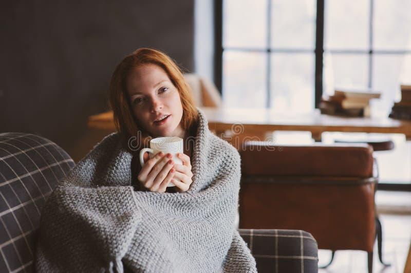 Giovane donna malata che guarisce con la bevanda calda a casa sullo strato accogliente fotografia stock