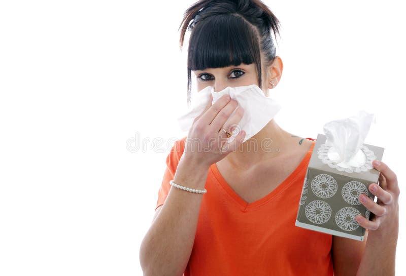 Giovane donna malata che soffia il suo naso su bianco fotografie stock