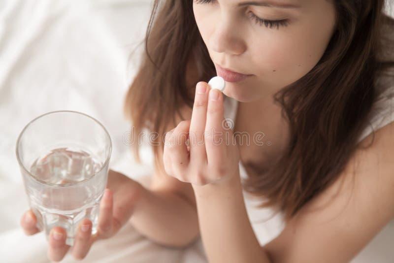 Giovane donna malata non sana che prende il sonnifero in pillole che si siede a letto fotografie stock libere da diritti