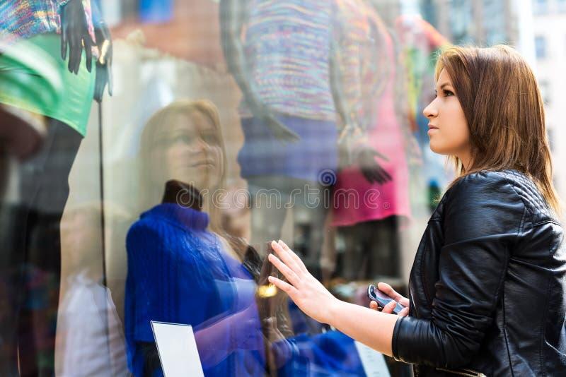 Giovane donna malinconicamente che esamina i vestiti fotografia stock