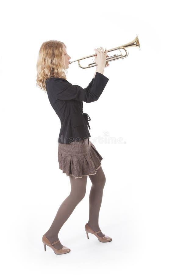 Giovane donna in mini vestito che gioca tromba fotografie stock