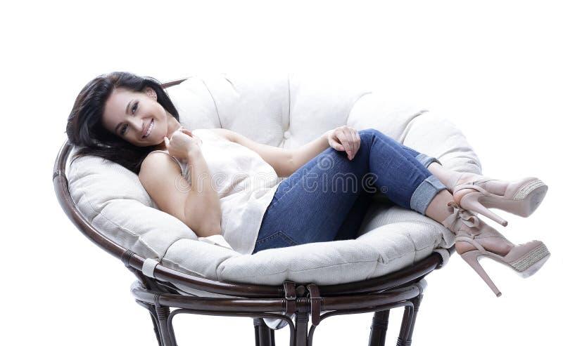 Giovane donna moderna che si rilassa in una sedia molle accogliente rotonda fotografie stock