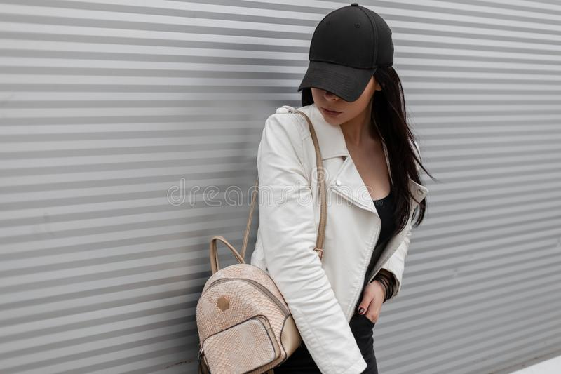 Giovane donna moderna graziosa in un berretto da baseball nero alla moda in un bomber bianco d'annata in jeans con uno zaino dell immagini stock libere da diritti