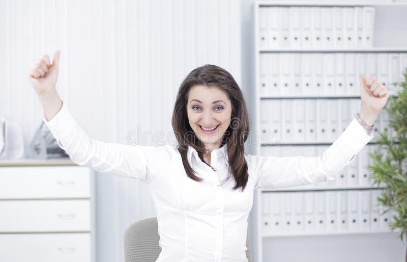 Giovane donna molto felice di affari che si siede al suo scrittorio fotografia stock libera da diritti