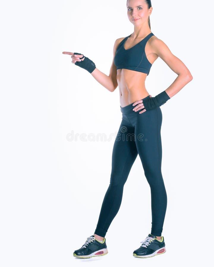 Giovane donna muscolare che posa in abiti sportivi contro il fondo bianco fotografia stock libera da diritti