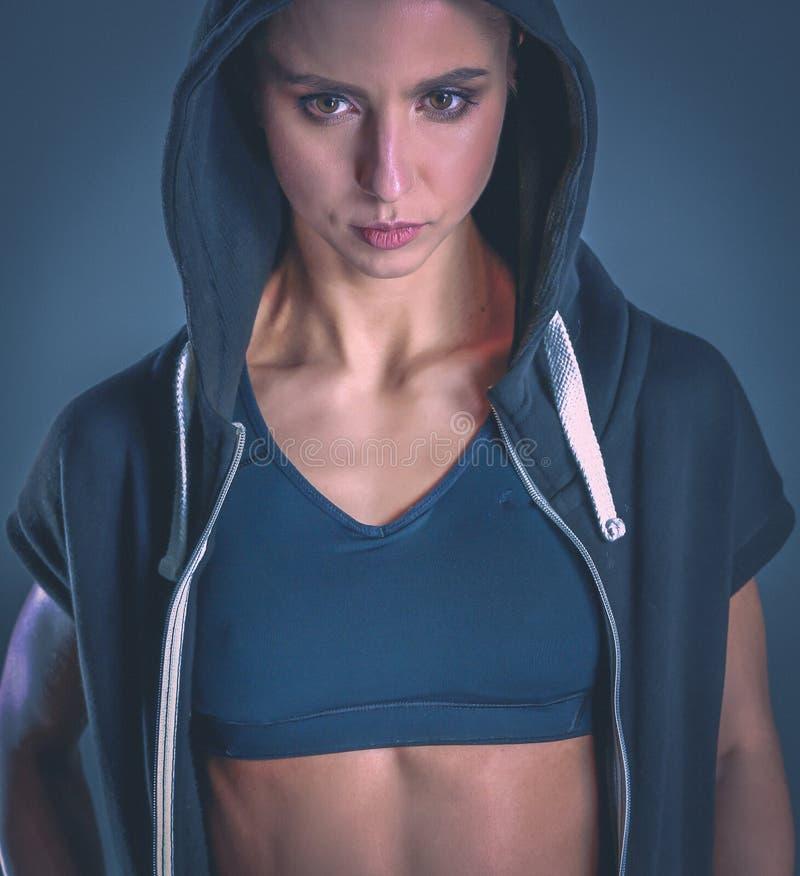 Giovane donna muscolare che posa in abiti sportivi contro il fondo nero fotografia stock libera da diritti