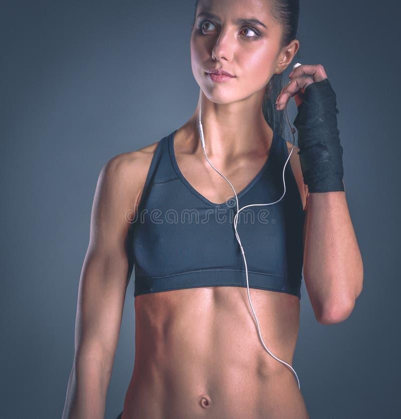 Giovane donna muscolare che posa in abiti sportivi contro il fondo nero immagine stock libera da diritti