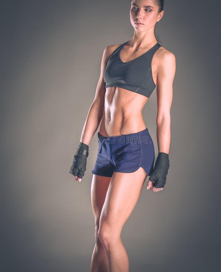 Giovane donna muscolare che posa in abiti sportivi contro il fondo nero immagini stock libere da diritti