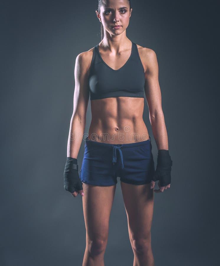 Giovane donna muscolare che posa in abiti sportivi contro il fondo nero fotografie stock