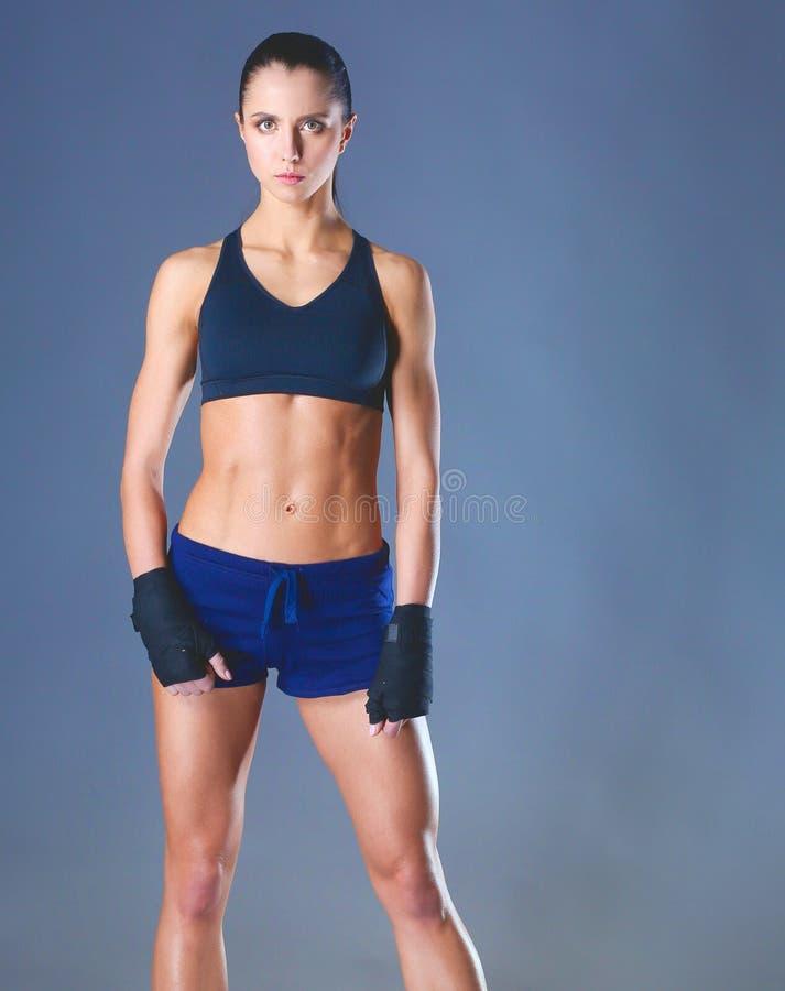 Giovane donna muscolare che posa in abiti sportivi contro il fondo nero fotografia stock
