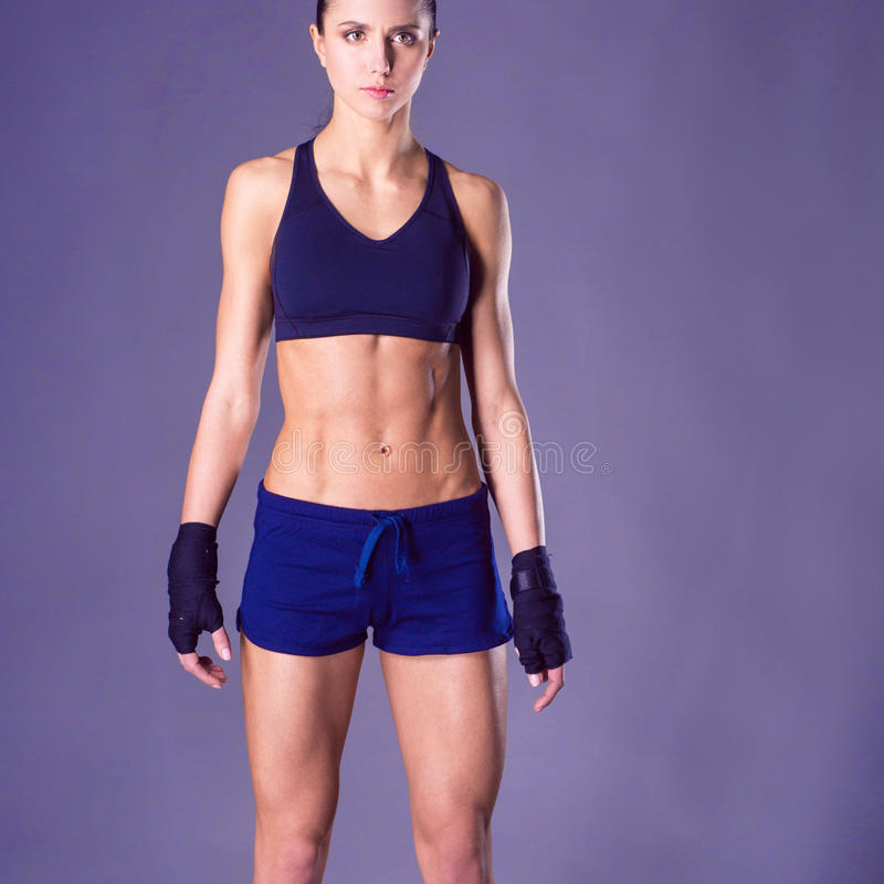Giovane donna muscolare che posa in abiti sportivi contro il fondo nero immagine stock