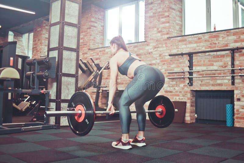 Giovane donna muscolare di forma fisica che fa deadlift pesante fotografia stock libera da diritti