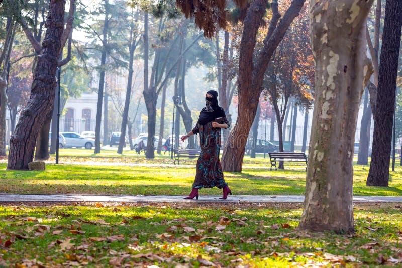 Giovane donna musulmana che cammina nel parco immagini stock