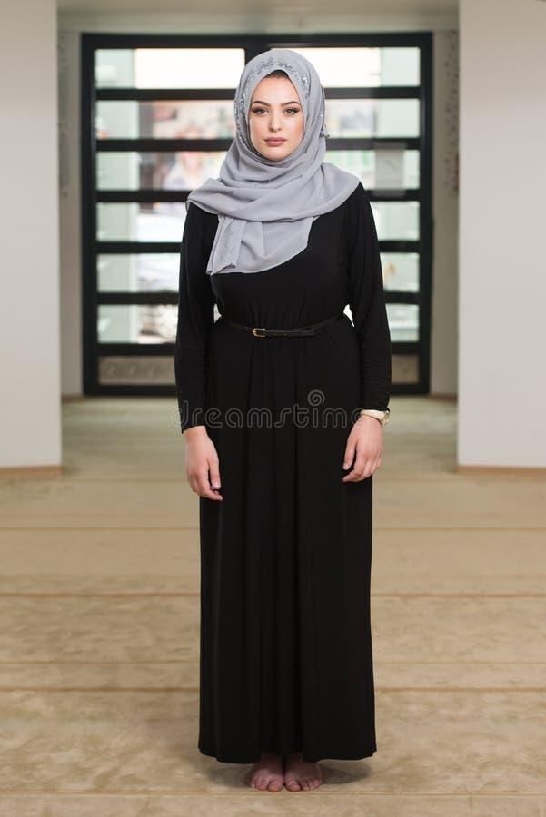 Giovane donna musulmana che prega nella moschea fotografia stock libera da diritti