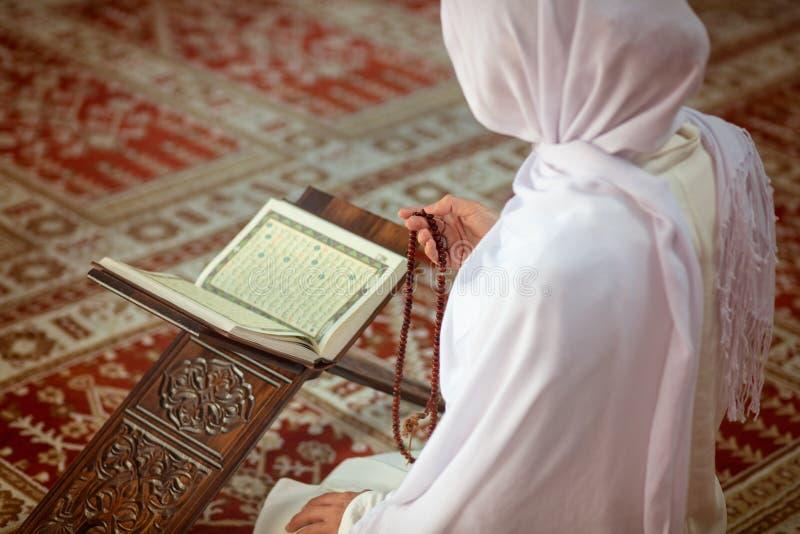 Giovane donna musulmana che prega nella moschea con il Corano fotografia stock